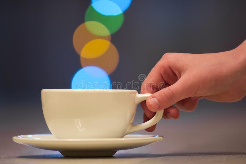 Hållande vit kopp kaffe för mänsklig hand med färgrik bokehånga arkivbild
