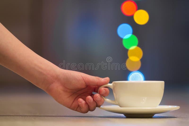 Hållande vit kopp kaffe för mänsklig hand med färgrik bokehånga royaltyfri bild
