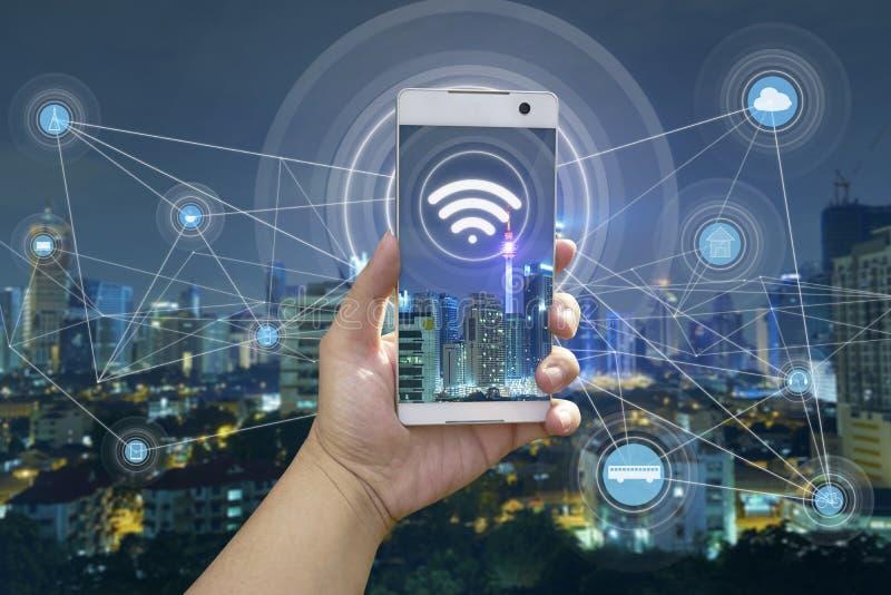 Hållande vit telefon för hand med stadsscape royaltyfria bilder