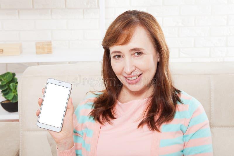 Hållande vit telefon för kvinnlig hand på den vita snabba banan inom hemmastadd bakgrund Mellersta ålderkvinna Kopieringsutrymme  arkivbilder
