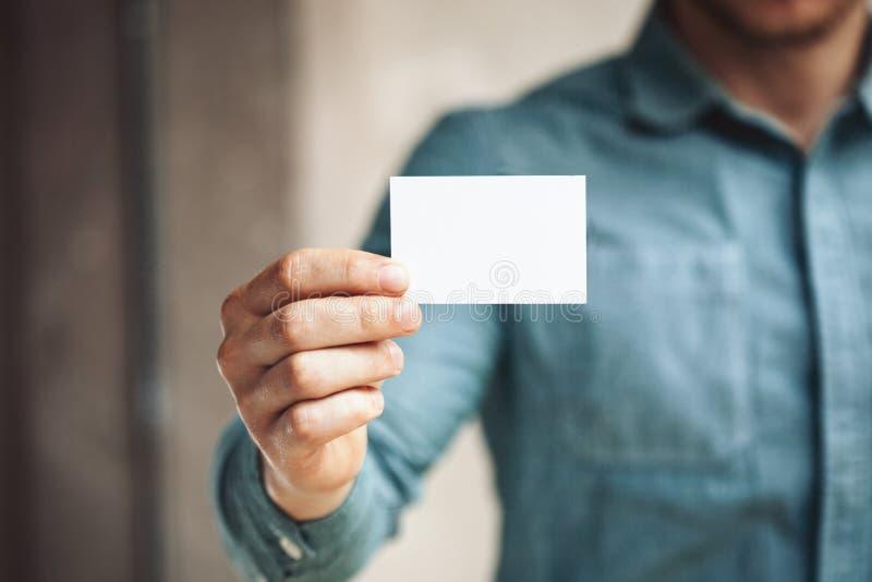 Hållande vitt affärskort för man på betongväggen royaltyfria bilder