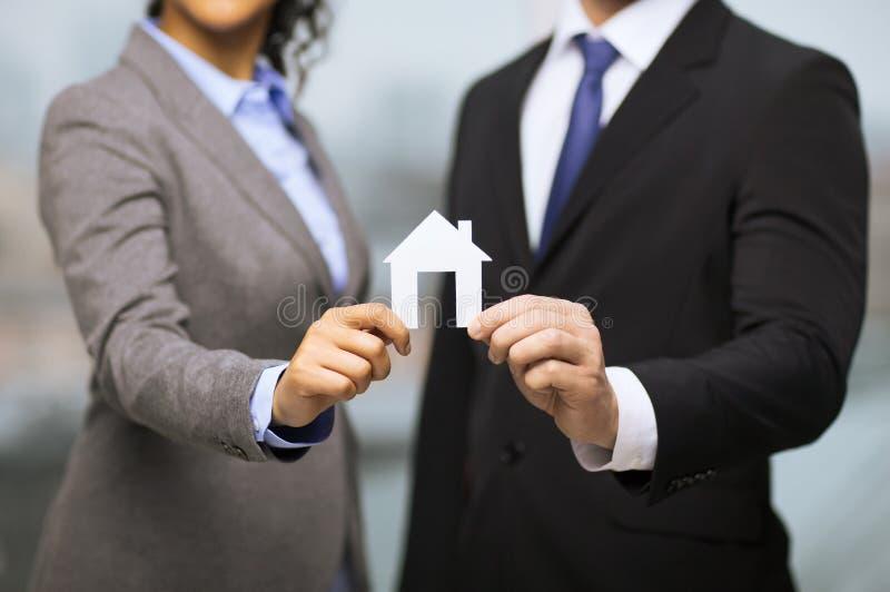 Hållande vitt hus för affärsman och för affärskvinna arkivfoto