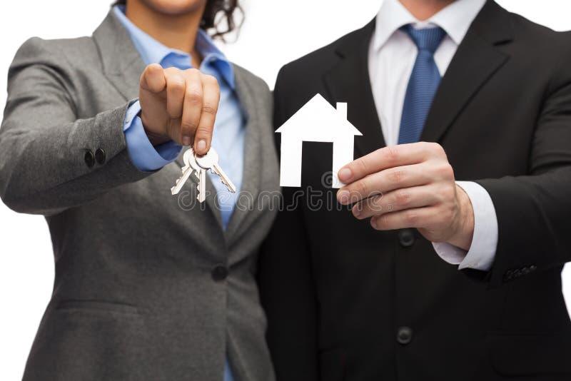 Hållande vitt hus för affärsman och för affärskvinna royaltyfri foto