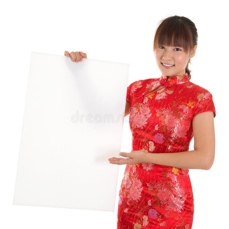 Hållande vitt tomt kort för kinesisk cheongsamflicka royaltyfri foto