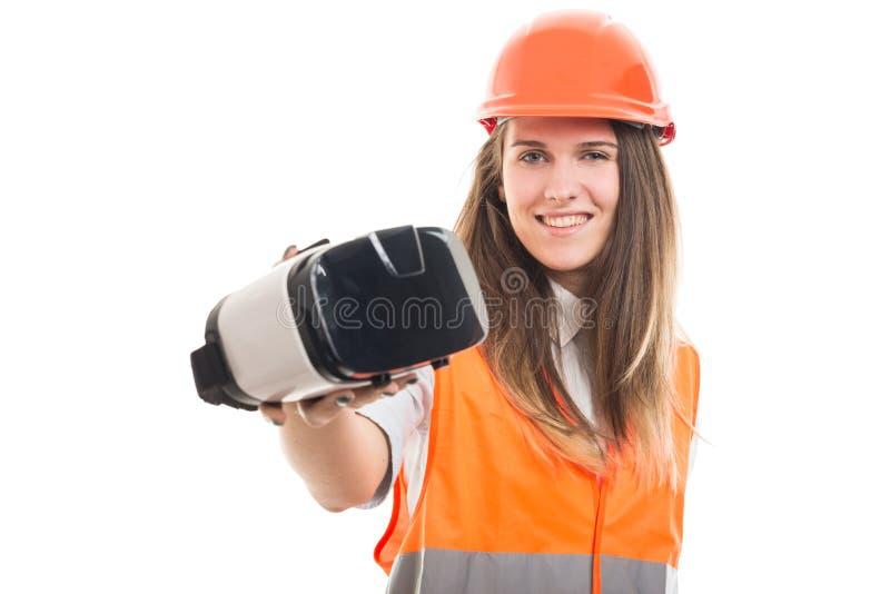 Hållande vrhörlurar med mikrofon för ung lycklig kvinnlig byggmästare royaltyfria foton