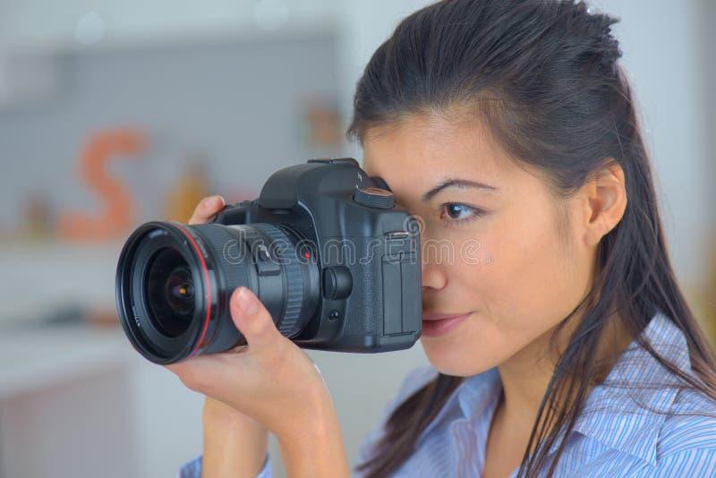 Hållande yrkesmässig kamera för kvinnlig fotograf arkivbild