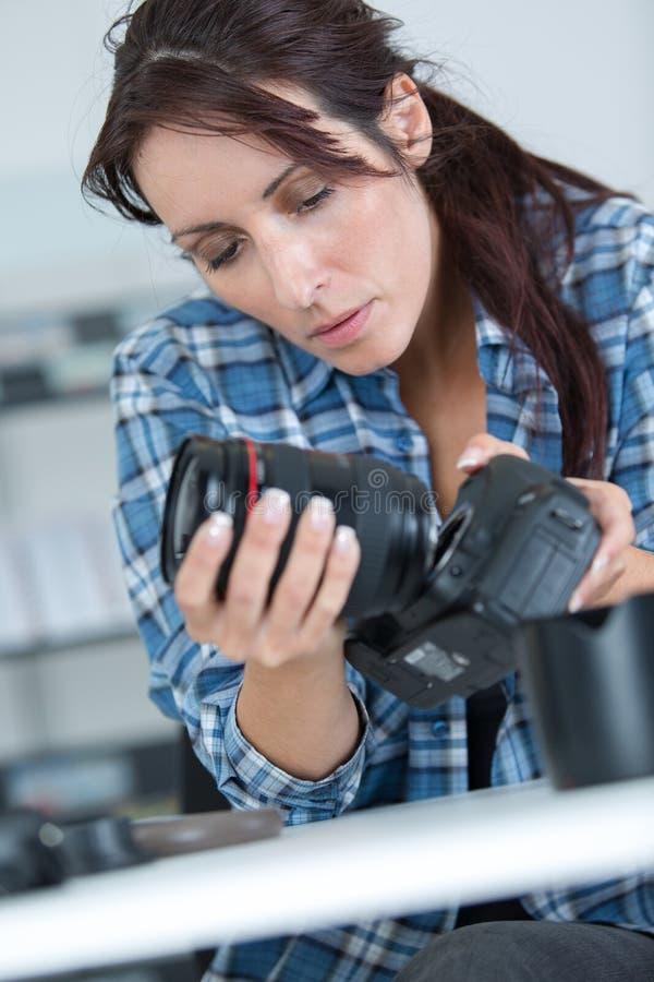 Hållande yrkesmässig kamera för kvinnlig fotograf - som isoleras över vit royaltyfri fotografi