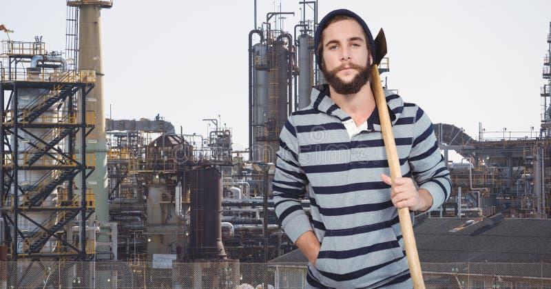 Hållande yxa för Hipster, medan stå mot fabrik royaltyfri bild