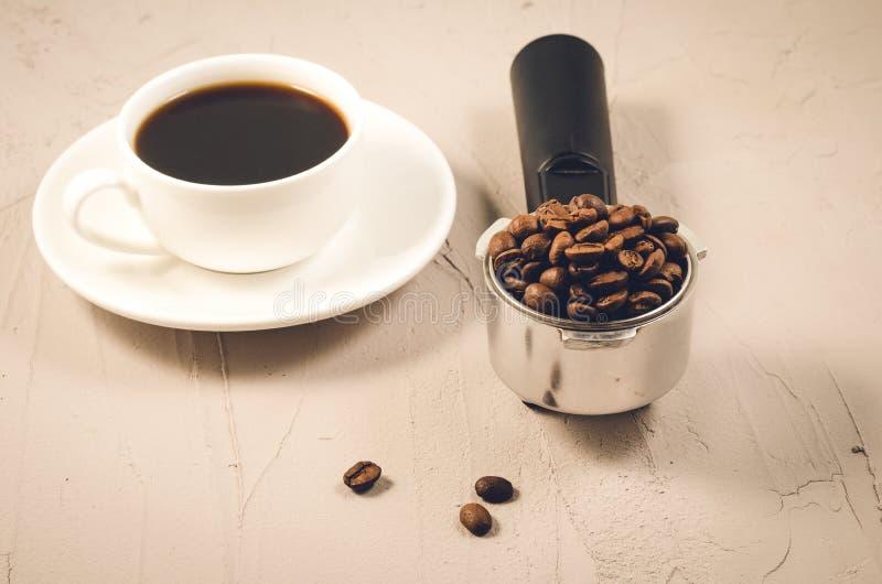 hållare som fylls med bönor och kaffekoppen/hållare som fylls med bönor och kaffekoppen på en stenbakgrund, selektiv fokus arkivfoto