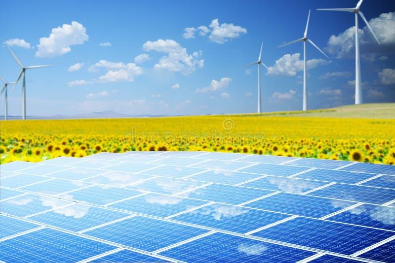 Hållbar energi från vindturbiner och solpaneler i lantligt landskap med solrosfältet royaltyfria foton