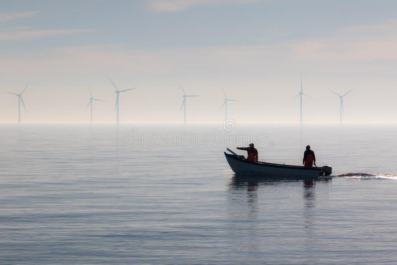 Hållbara resurser Liten fiskebåtöverskrift ut till havet arkivbild
