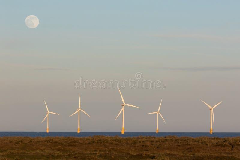 Hållbara resurser Vindturbiner till havs som producerar el natt och dag fotografering för bildbyråer