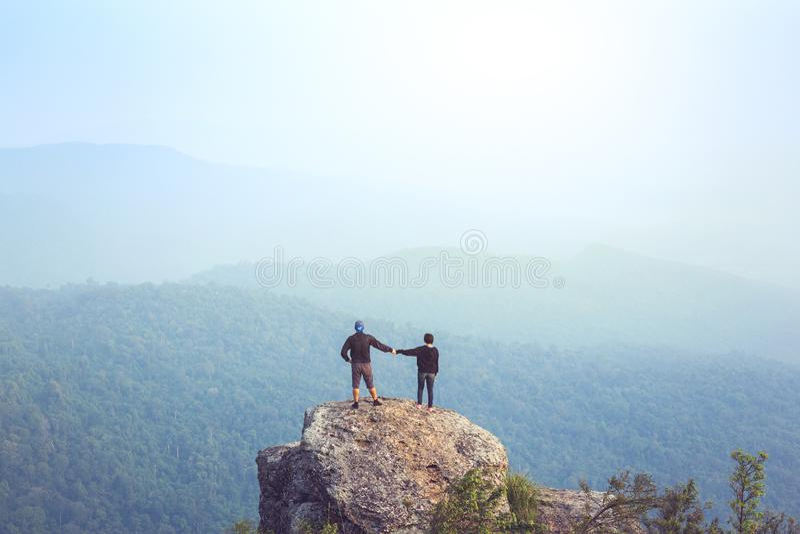 Håller ögonen på den Asien för den unga mannen för det Instagram filtret turisten på berget över den dimmiga och dimmiga morgonso arkivfoto