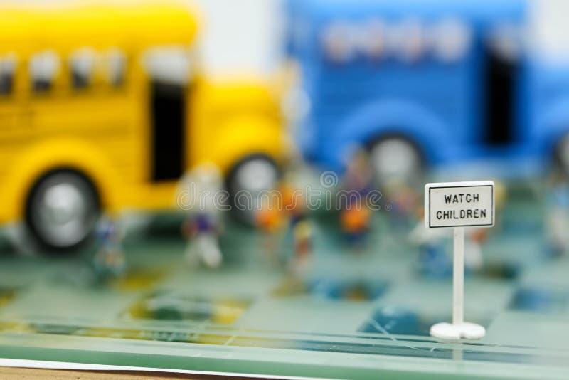 Hållplatsen undertecknar med suddighet av läraren och en grupp av elementär sc royaltyfri foto