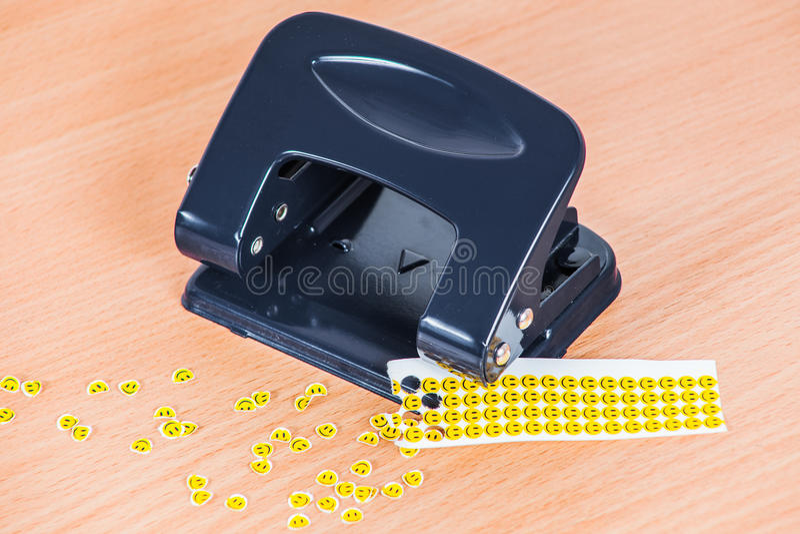 Hålstansmaskin och pressade ut pappersleenden på tabellen fotografering för bildbyråer