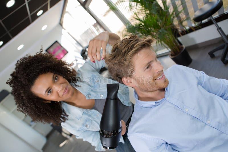 Hår för klienter för kvinnlig frisörslaguttorkning manligt arkivbild