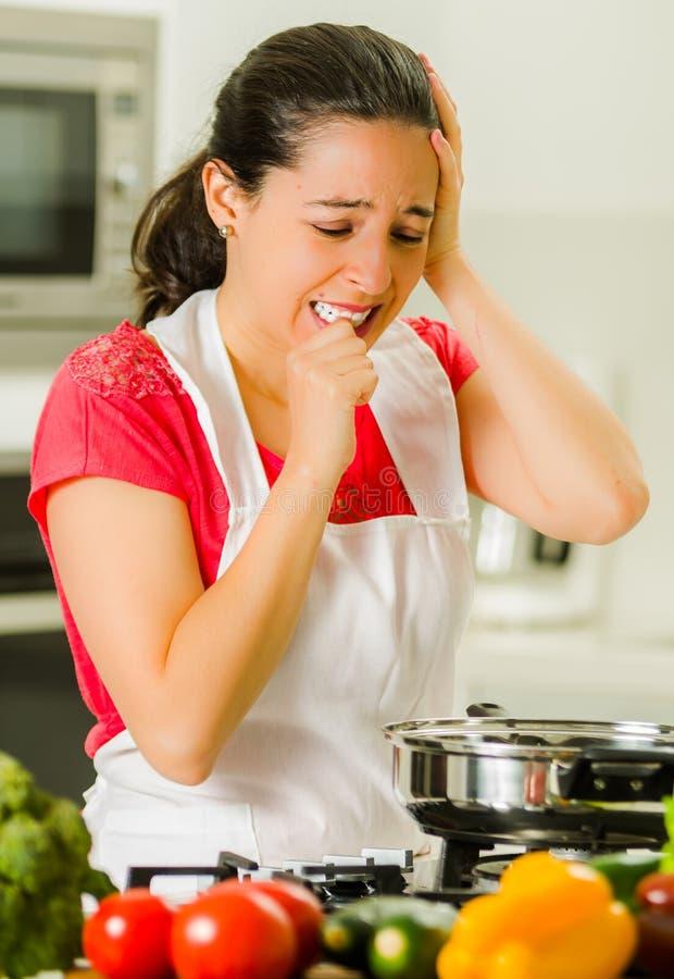 Hår för kock för ung kvinna hållande i frustration, missmodigt ansiktsuttryck, tabell med kokkärlet och grönsaker arkivbild