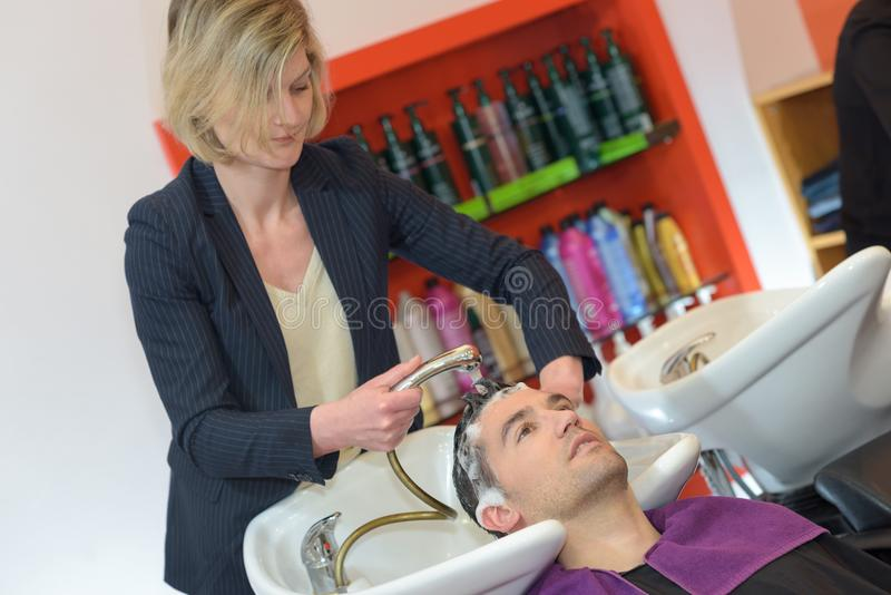 Hår för kunder för kvinnlig frisörfrisörtvagning manligt royaltyfri bild