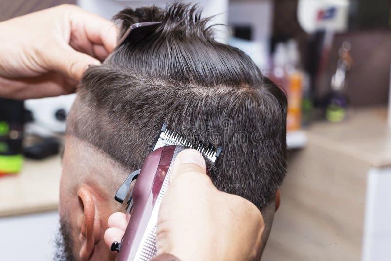 Hår för man` som s utformar och ansar med hjälpen av sax maskin och hårnagelsax i hårsalongen royaltyfri fotografi