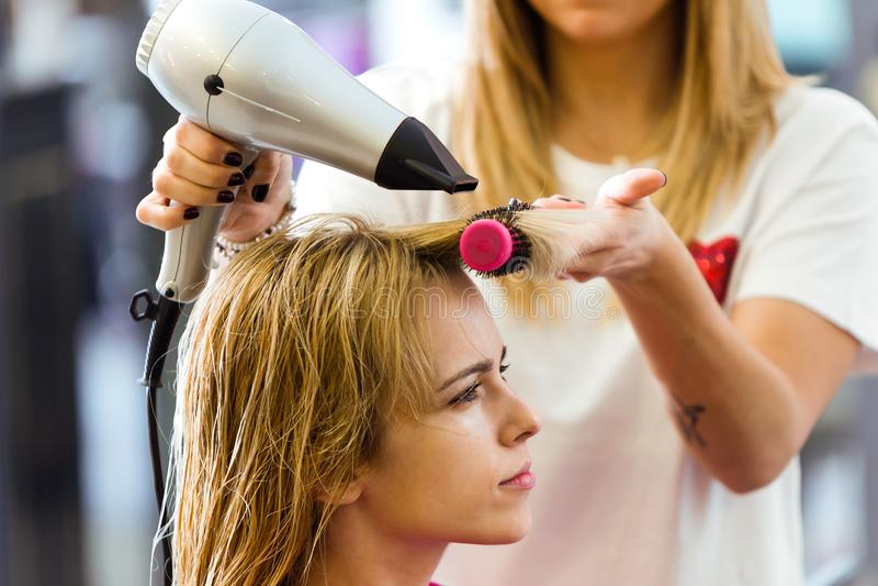 Hår för ` s för kund för frisöruttorkning kvinnligt i skönhetsalong arkivfoton