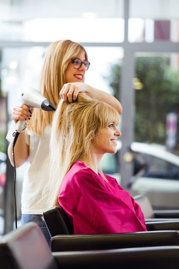Hår för ` s för kund för frisöruttorkning kvinnligt i skönhetsalong arkivbilder
