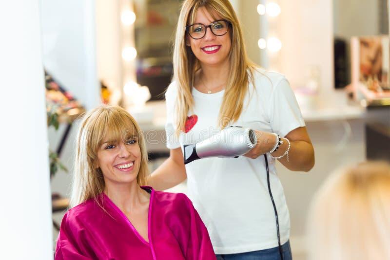 Hår för ` s för kund för frisöruttorkning kvinnligt i skönhetsalong royaltyfri foto