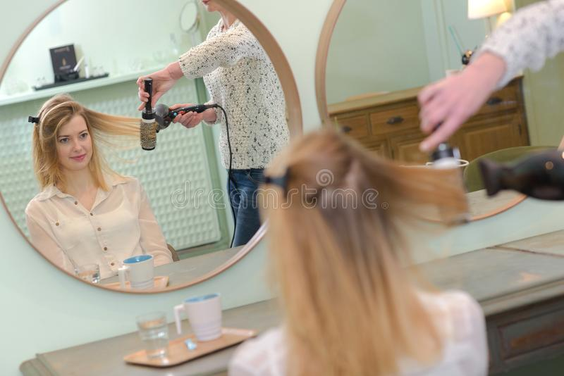 Hår för stylistuttorkningkvinna i skönhetsalong arkivfoton