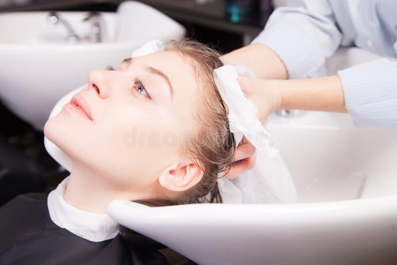 Hår för stylistuttorkningkvinna med handduken i salong arkivfoton