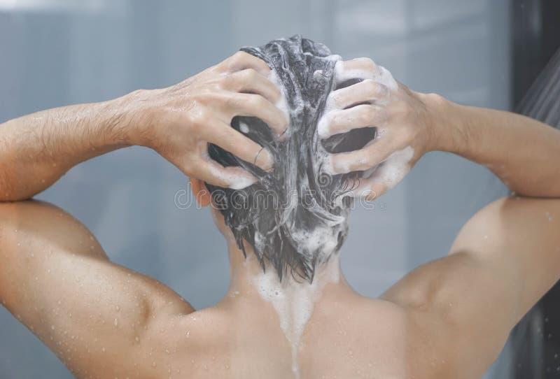 Hår för ung man för Closeup tvättande med med schampo i badrummet, tappningsignal, selektiv fokus arkivfoton