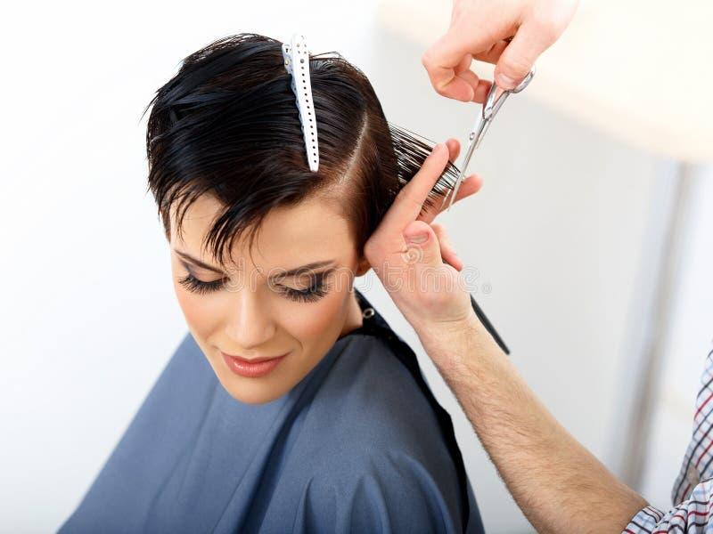Hår. Frisör Cutting Woman Hair i skönhetsalong. Frisyr royaltyfri bild
