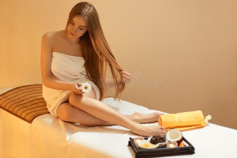 hår Härliga blonda omsorger om hennes hår Spa salong royaltyfria bilder