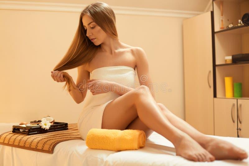 hår Härliga blonda omsorger om hennes hår Spa salong royaltyfri bild