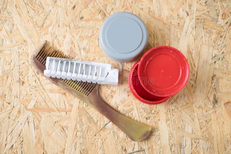 Hår stelnar och hårborsten på den wood tabellen arkivfoto