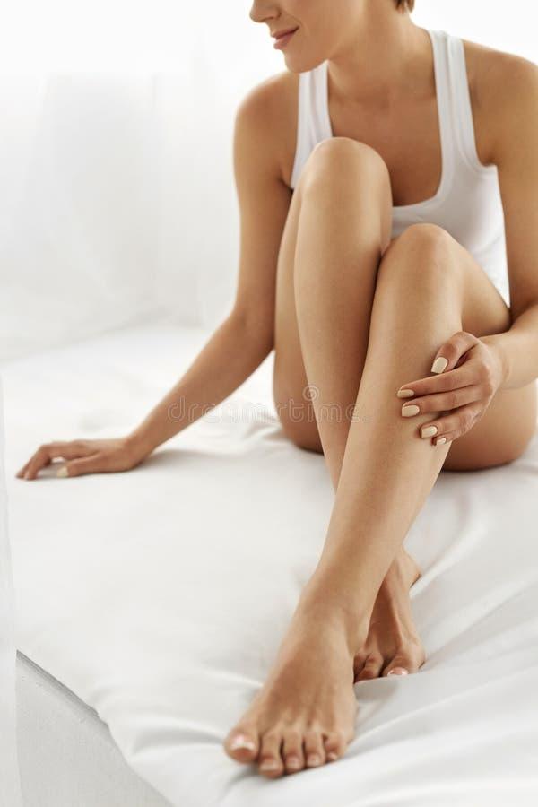 Hårborttagning Slutet upp kvinna räcker rörande långa ben, mjuk hud royaltyfri fotografi