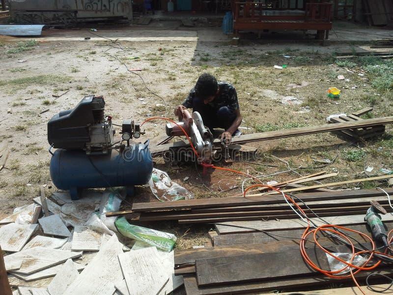 Hård funktionsduglig snickare som klipper träplankan arkivbilder