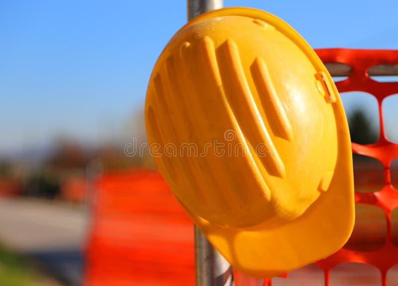Hård hatt på vägkonstruktionsplatsen under vägarbeten royaltyfri bild