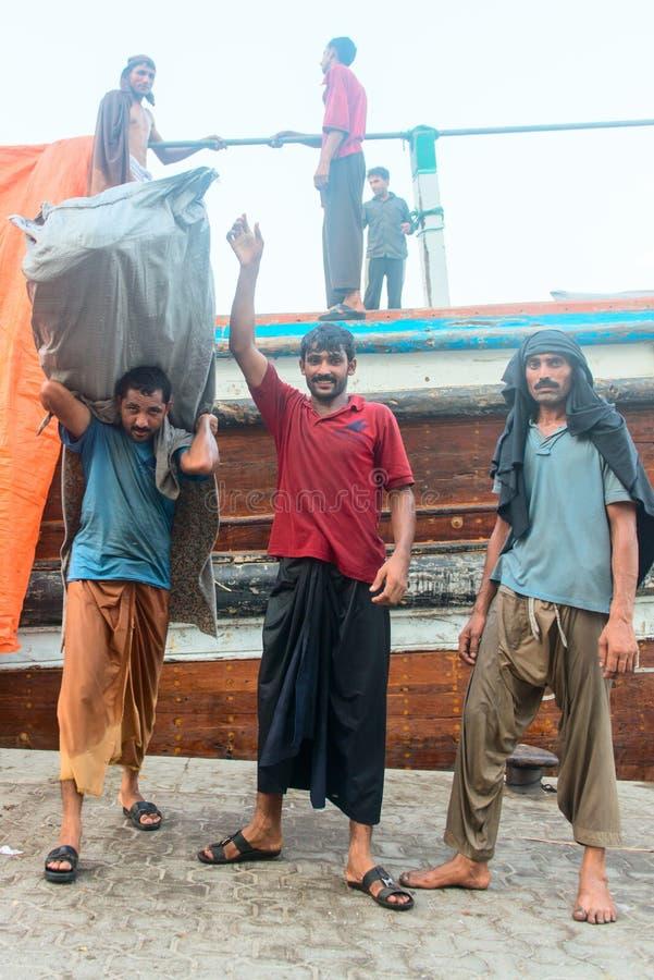 Hårda funktionsdugliga hamnarbetare i traditionell dhowwharfage port royaltyfri bild