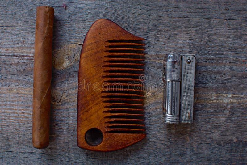 Hårkam för ett skägg, en cigarr och tändarelögner på en träbakgrund arkivbild