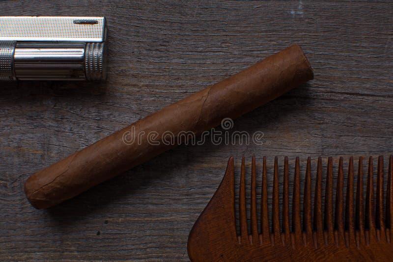 Hårkam för sigar och tändarelögner för ett skägg, på en träbakgrund royaltyfria bilder