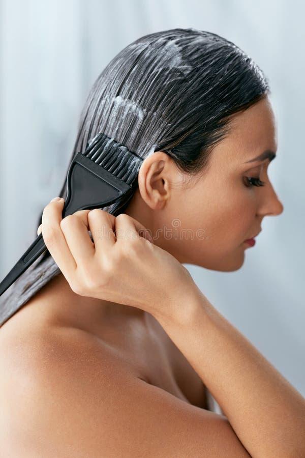 Hårmaskering Kvinna som applicerar hårbalsamen på långt hår med borsten, behandling för håromsorg arkivbilder