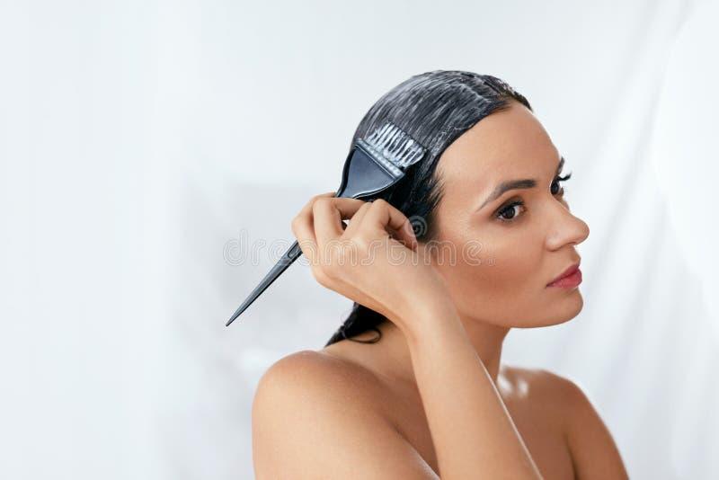 Hårmaskering Kvinna som applicerar hårbalsamen på långt hår med borsten, behandling för håromsorg royaltyfri bild