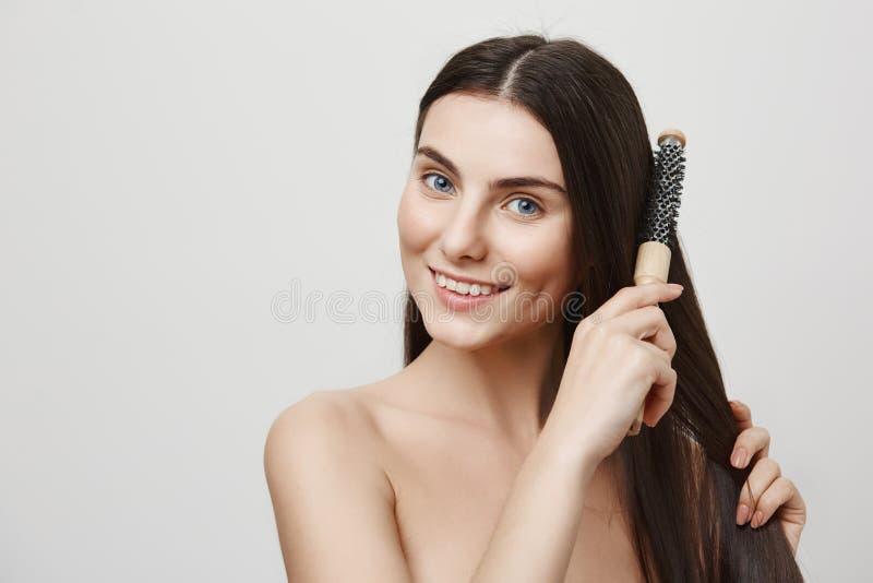 Hårsalong och skönhetbegrepp Inomhus stående av den lyckliga attraktiva caucasian kvinnan som borstar hår med borsten och att le fotografering för bildbyråer