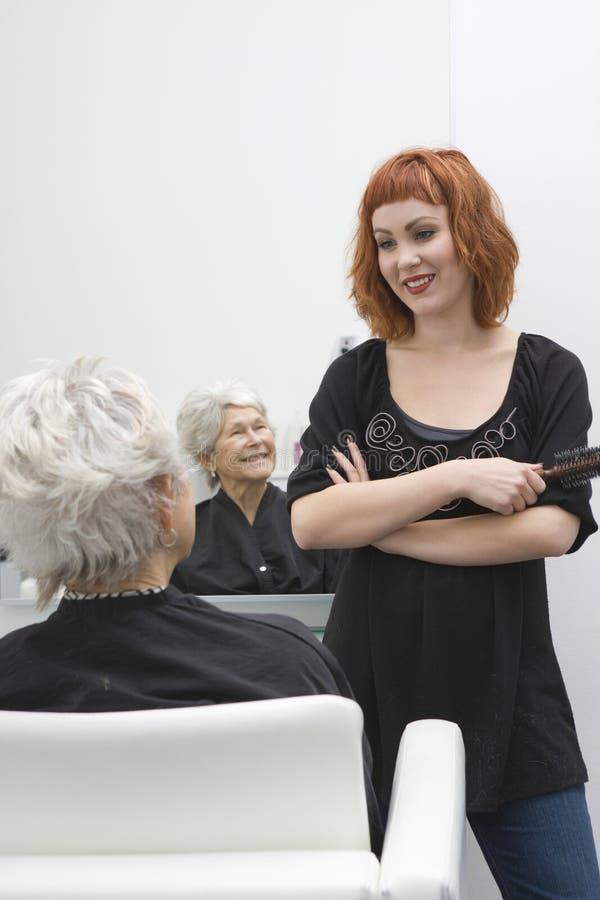 Hårstylist som diskuterar med den höga kvinnan arkivfoto
