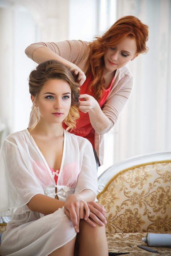 Hårstylist som förbereder den härliga bruden för bröllopet arkivbild