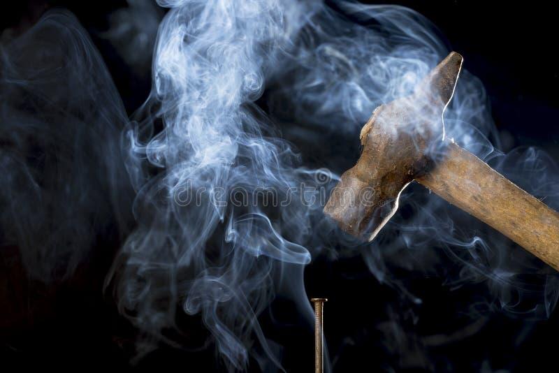 Hårt arbetebegrepp Det abstrakta fotoet av den rostiga hammaren för metall över spikar med rök på svart bakgrund arkivfoto