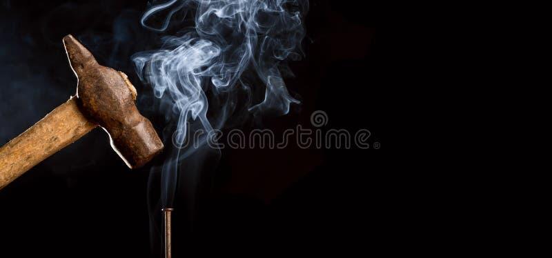 Hårt arbetebegrepp Det abstrakta fotoet av den rostiga hammaren för metall över spikar med rök på svart bakgrund kopiera avstånd arkivfoto