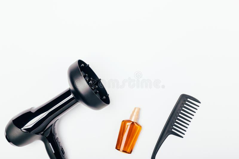 Hårtork med diffusordysan, flaska av att uppföda olja royaltyfria bilder