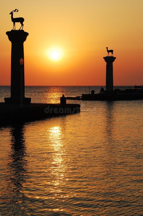 Hébergez les portes et le phare, Rhodes, coucher du soleil photographie stock