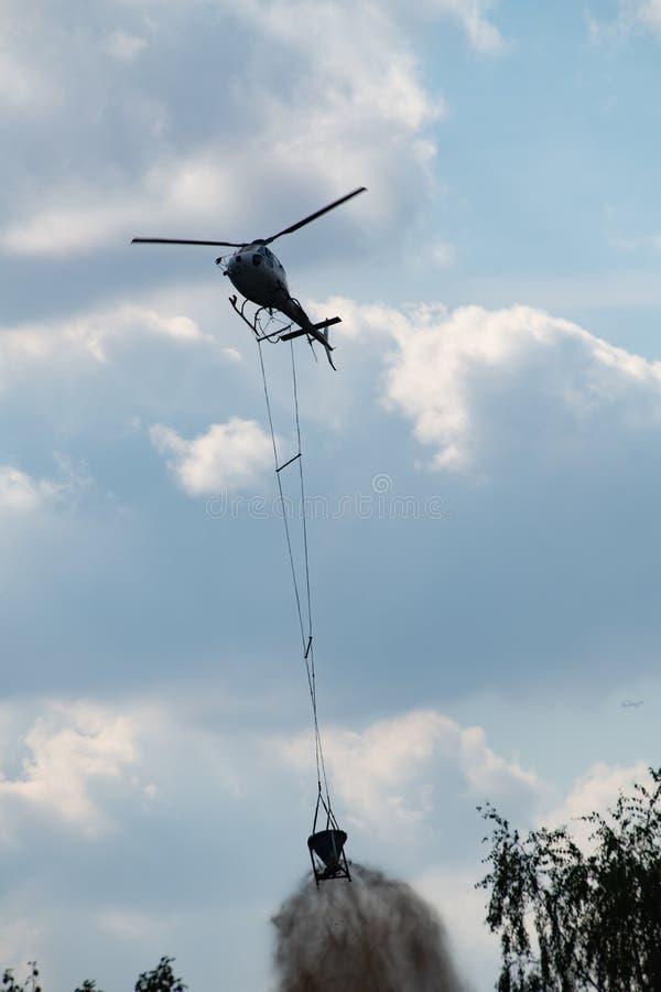 Hélicoptère avec la craie de chute de seau au-dessus de la forêt pour améliorer le sol acide photographie stock