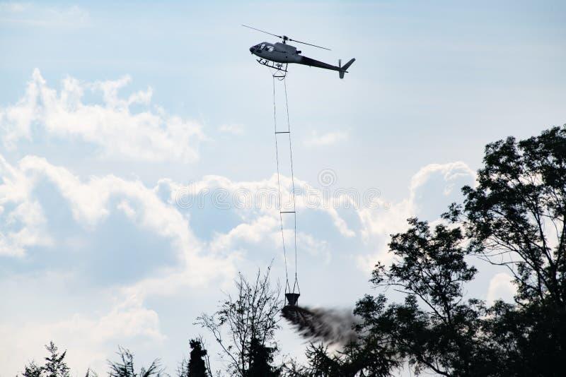 Hélicoptère avec la craie de chute de seau au-dessus de la forêt pour améliorer le sol acide photo libre de droits